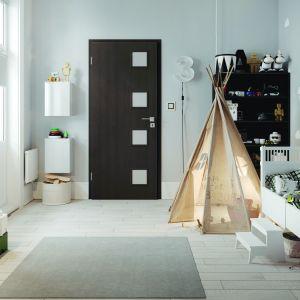 Drzwi Modena 4 stanowią estetyczne uzupełnienie każdej przestrzeni mieszkalnej. Występują w wielu drewnianych dekorach, a ich wyróżnikiem są kwadratowe płyciny w kolorze skrzydła i szyby mleczne hartowane. Dzięki wzmocnionej konstrukcji staną się wieloletnią ozdobą wnętrza. Cena: od 344 zł. Dostępne w ofercie firmy Classen. Fot. Classen