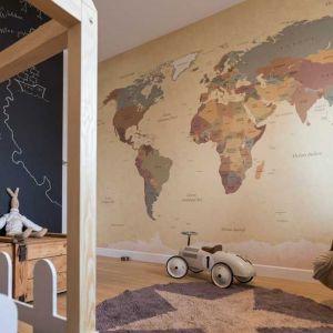 Tapeta z mapą świata na ścianie, kufer, model samochodu – po tym pokoju od razu widać, jakie są zainteresowania młodego mieszkańca. I że uwzględniono je, aranżując wnętrze! Każde dziecko lubi zarysowywać duże powierzchnie, dając upust swej wenie twórczej. Żeby nie musieć w kółko odnawiać ścian, warto jedną z nich pomalować farbą tablicową. Na niej będzie mógł mazać do woli. Fot. Pracownia Architektoniczna MGN