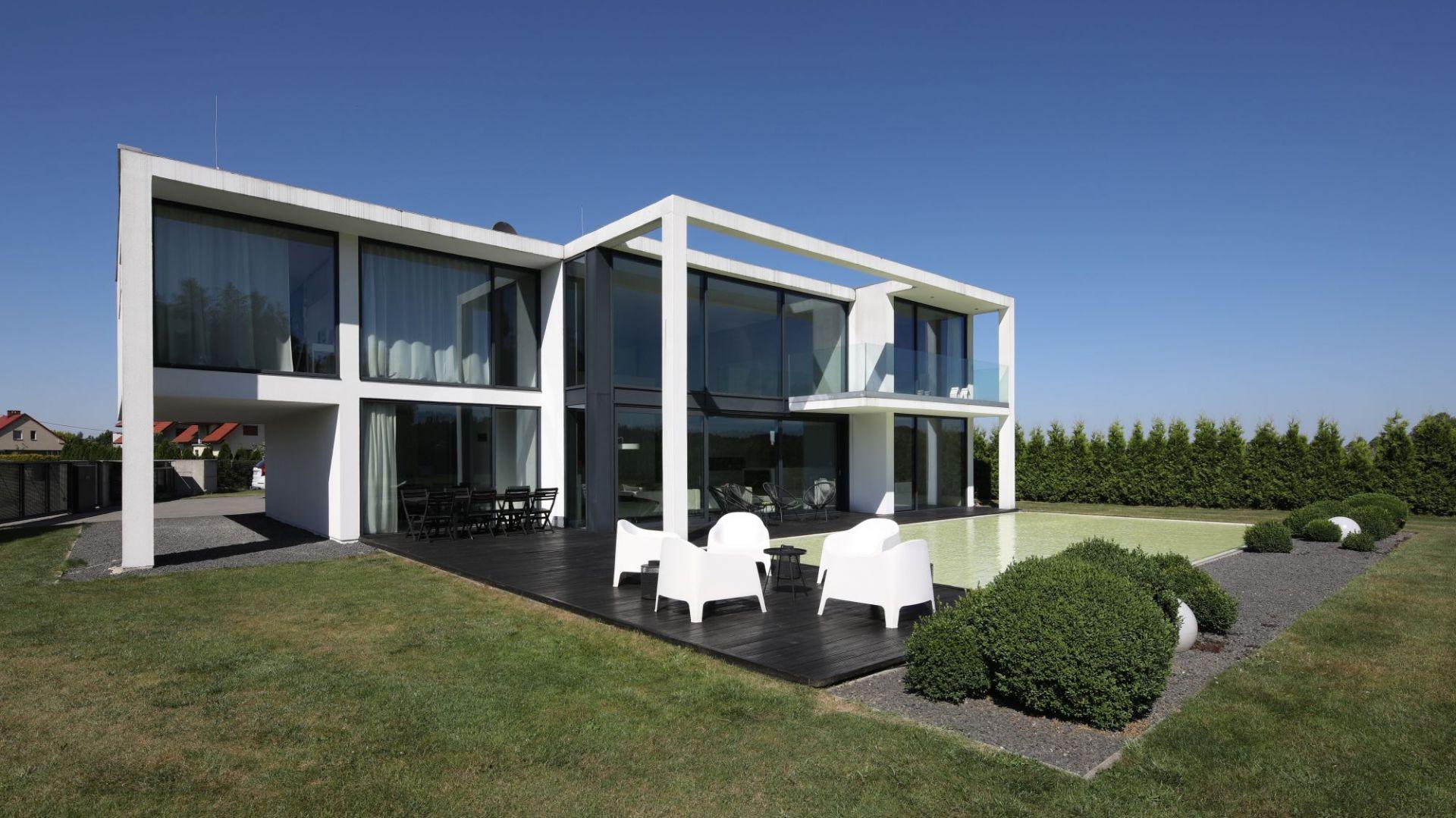 Beton House to dwupiętrowa bryła o prostej formie i białej kolorystyce. Od strony ogrodu dominują tu duże, dwukondygnacyjne przeszklenia. Projekt: arch. Hanna i Seweryn Nogalscy, Beton House Architekci. Fot. Bartosz Jarosz