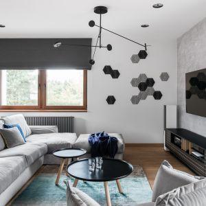 Tło dla barwnych akcentów w postaci dywanu i dodatków stanowi stonowana, monochromatyczna baza kolorystyczna. Projekt: Estera i Robert Sosnowscy. Fot. FotoMohito
