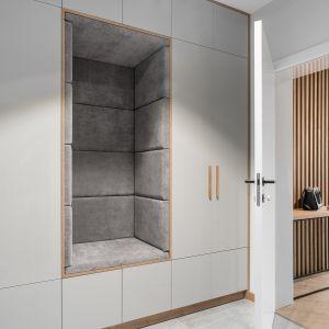 Białą zabudowa w holu została ocieplona drewnem i szarą tapicerką. Projekt: Estera i Robert Sosnowscy. Fot. FotoMohito