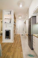 W przedpokoju wydzielony regał, biokominek na salon i pijemna szafa na sypialnię - projekt GACKOWSKA DESIGN