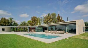Parterowy dom w hiszpańskim regionie Costa Blanca zwraca uwagę nowoczesną fasadą o otwartym charakterze.Sięgające od podłogi do sufitu przeszklenia otwierają rozległe widoki na ogród z basenem i tworzą modny efekt przenikania się wnętrza z