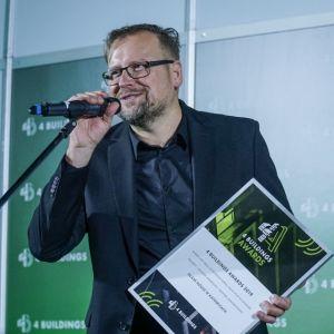 """Seweryn Nogalski, właściciel Beton House oraz architekt domu Glass House, odbiera nagrodę w kategorii """"Projekty - Budynek mieszkalny / budynek jednorodzinny"""". Fot. PTWP/Michał Oleksy"""