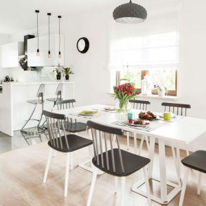 W jadalni do dużego białego stołu dopasowano bukowe krzesła patyczaki na białych nogach z czarno-szarym siedziskiem i oparciem. Fot. makehome.pl