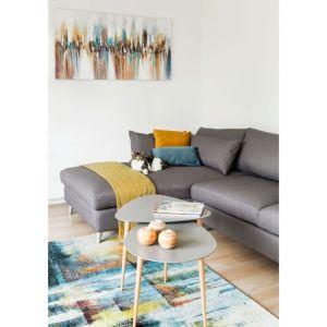 Przy sofie nie mogło zabraknąć stolików kawowych również w szarym kolorze. Ich bukowe nogi pasują do drewnianej podłogi i komody pod telewizorem, którą wyróżniają kolorowe fronty. Fot. makehome.pl