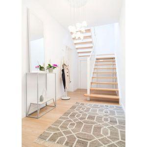 W korytarzu znalazła się stylowa konsolka. To bardzo elegancki i praktyczny mebel, a jego ażurowa konstrukcja sprawia, że nie przytłacza pomieszczenia. Fot. makehome.pl