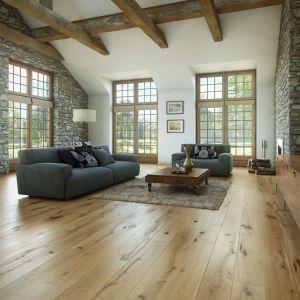 """Domy z poddaszem użytkowym """"oferują"""" niesztampowe możliwości aranżacji wnętrz. Tu prezentujemy salon z odkrytą konstrukcją więźby dachowej, która doskonale prezentuje się z trójwarstwowym parkietem drewnianym i okładziną kamienną. Fot. Barlinek"""