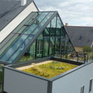 Oszczędna bryła wcale nie musi być nudna. Ciekawe przeszklenia dachu i elewacji są niezwykle eleganckim uzupełnieniem. Projekt: arch. Laure Levanneur, agence ARCHIfact, Fot. Thierry Mercier