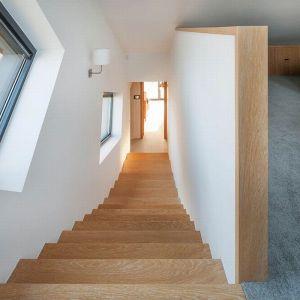 Okna wzdłuż biegu schodów doskonale doświetlają klatkę a kształtem podkreślają dynamikę bryły, która wraz ze schodami unosi się do góry. Proj. Domo Dom, Fot. Tomasz Zakrzewski