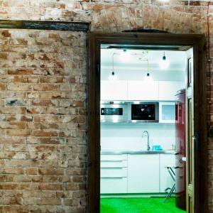 """Ściana pomiędzy salonem i kuchnią została odsłonięta i pozostawiona w """"surowej"""" formie."""