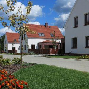 """Sześć białych domów stojących przy malowniczej drodze w pobliżu Jeziora Turawskiego do złudzenia przypomina typowe """"jamniki"""", wydłużone budynki, jakie można spotkać w prawie każdej opolskiej wiosce."""