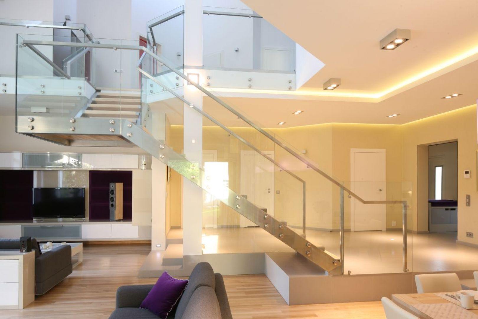 Schody, w zależności od koncepcji na urządzenie wnętrza naszego domu, możemy pięknie wyeksponować lub ukryć. Tu dzięki szklanym balustradom i modnym stalowym wykończeniom schody prezentują się niezwykle pięknie. Proj. Monika i Adam Bronikowscy, Fot. Bartosz Jarosz