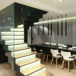 Tu dwubiegowe schody z przeszkloną balustradą ulokowano w centrum strefy dziennej. Interesującym tłem dla klatki schodowej jest ściana wykończona cegłą. Proj. Dominik Respondek, Fot. Bartosz Jarosz