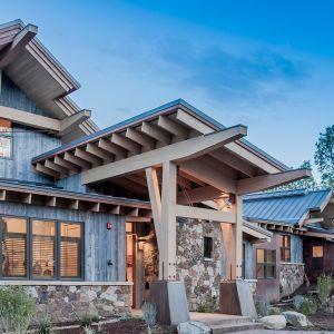 Strefę wejściową zdobi ciekawie zaprojektowany podcień. Surowe belki konstrukcyjne, beton i kamień, pomimo że są ciężkimi materiałami, w tym połączeniu nadają uroku i wcale nie przytłaczają bryły domu. Fot. Tim Stone,  Kelly & Stone Architects