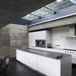 Surowy beton na ścianie i szary, kamienny blat pięknie komponują się z białą zabudową kuchenną. Wnętrze prezentuje się bardzo elegancko. Fot. Pfleiderer