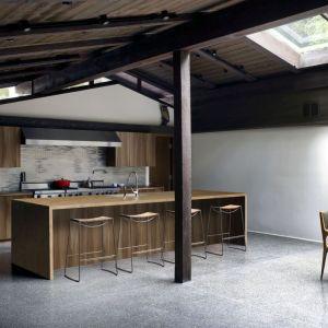 Metaliczna ściana nad blatem kuchennym, surowa więźba dachowa i słupy konstrukcyjne decydują o wyjątkowym charakterze tego wnętrza. Fot. Pfleiderer