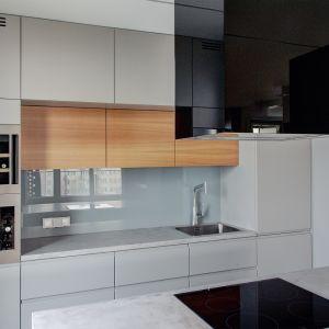 Szara zabudowa kuchenna pięknie prezentuje się z elementami drewnianych frontów. Beton w tej kuchni wykorzystano do wykończenia wyspy i blatów. Fot. Bautech