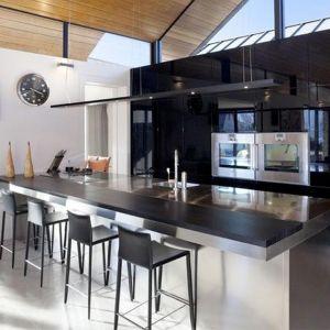 Kuchnię z wyspą urządzono w bardzo nowoczesnym, minimalistycznym stylu. Dominują w niej biel, czerń i stal. Fot. M&W