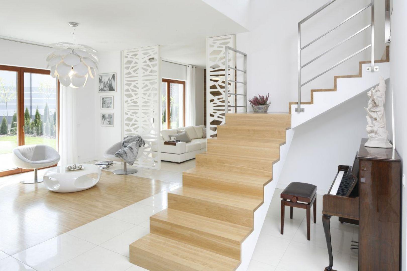 Piękne dwubiegowe schody, których stopnie wykończono tym samym gatunkiem drewna, co podłogę w salonie. Ich słomkowy kolor przepięknie komponuje się z białym wnętrzem. Proj. Agnieszka Ludwinowska, Fot. Bartosz Jarosz