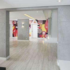 Jasne minimalistyczne wnętrze wypełnione bialą i betonem ozdobiono wyjątkowyo barwnumi grafikami. Proj. Dominik Respondek, Fot. Bartosz Jarosz