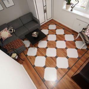 W salonie pojawiło się jeszcze kilka dodatków zgranych z wnętrzem – mały stolik, kontrastujący fotel i nadające przytulności tkaniny. Fot. Ania Drozd