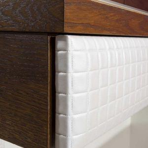 Innym interesującym rozwiązaniem są elementy tapicerowane tkaniną obiciową lub skórą ekologiczną. Zestawienie ciemnych frontów w wybarwieniu orzecha antycznego z geometrycznym deseniem w kolorze wanilii tworzy naprawdę udaną kompozycję. Fot. Mebin