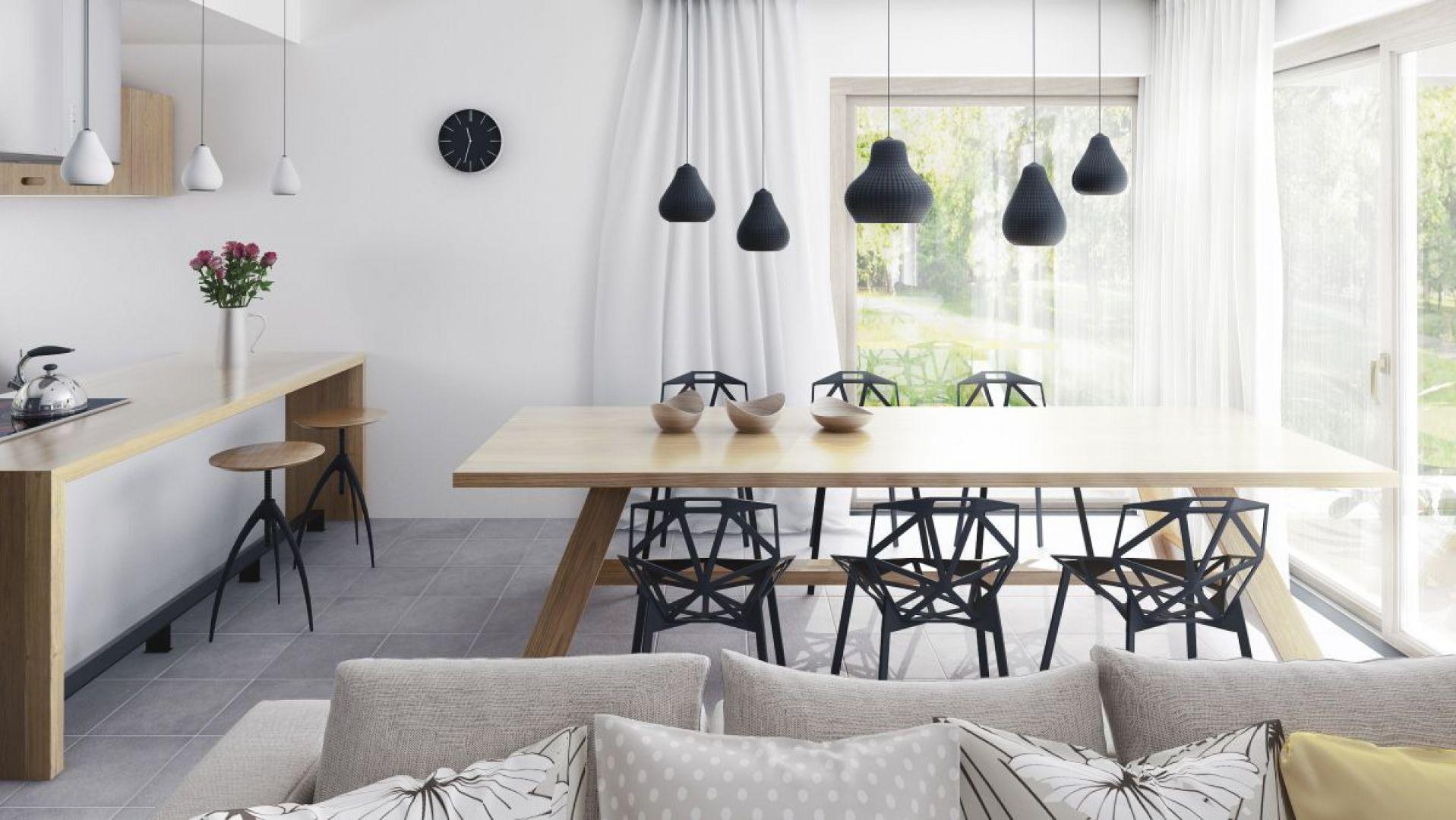 """Jadalnia to najjaśniejszy punkt strefy dziennej. Usytuowana w przeszklonym narożniku """"zaprasza"""" do rodzinnego spędzania czasu. Akcentem kontrastującym są tu nowoczesne elementy wyposażenia – nowoczesne krzesła, czarne i białe lampy. Fot. Dobre Domy"""