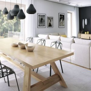 Funkcjonalny podział na strefy wyznacza też wykończenie podłogi - w jadalni zaproponowano szary gres, w salonie ciepłą drewnianą deskę. Fot. Dobre Domy
