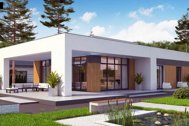Parterowy, nowoczesny dom z płaskim dachem, z garażem jednostanowiskowym i odwróconym układem pomieszczeń, gdzie sypialnie rozplanowano w skrzydle od frontu. Elewację wykończono w bieli, szarościach oraz drewnie.Projekt Zx185 przeznaczony jest d