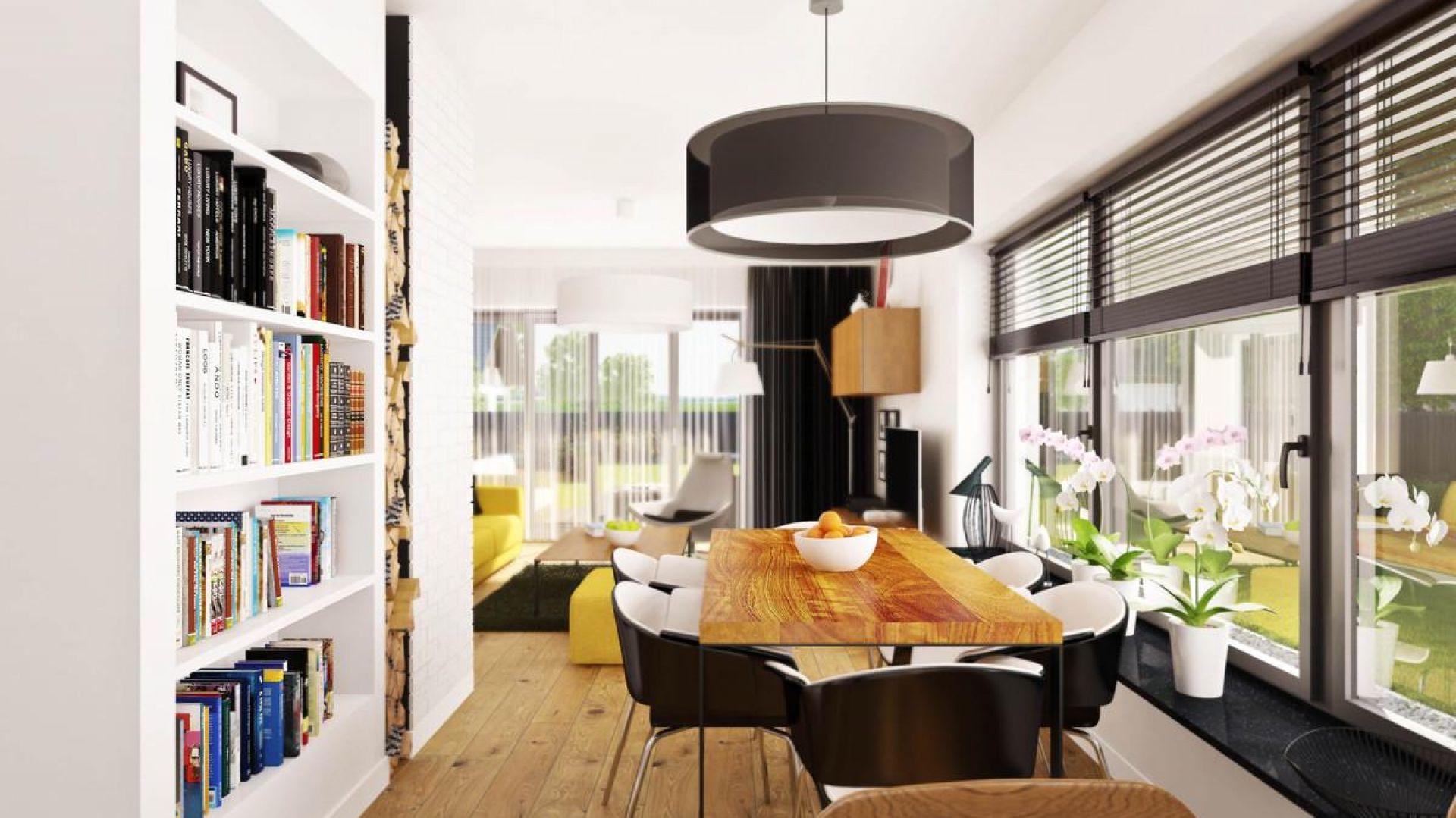 W centrum jadalni stoi duży, drewniany stół. Nad nim zawieszono czarny, elegancki żyrandol. Fot. Prestige
