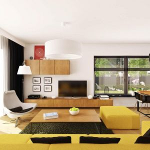 W salonie dominuje biel. Nie brak tu jednak także innych kolorów. Jaskrawy żółty, czarny doskonale pasują do tego wnętrza. Dodatkowo ocieplono je drewnem. Fot. Prestige