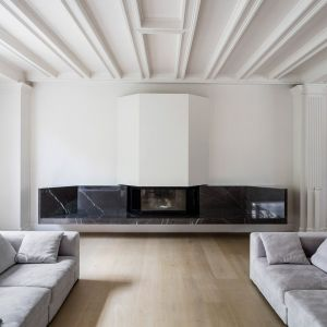 Białe, historyczne otwarte wnętrza ociepla drewniana podłoga oraz luksusowy kominek z kamienia. Fot. Adrià Goula Sardà