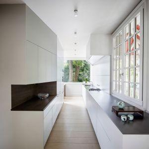 Długa, wąska kuchnia została zabudowana delikatnymi białymi meblami. Nawet tu architekci tak rozmieścili poszczególne elementy wyposażenia, aby nie zasłaniały pięknego widoku na przepiękny ogród. Fot. Adrià Goula Sardà