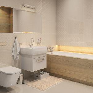 Wanna obita jest jasnym drewnem. Podobnie wnętrze półki wydrążonej w ścianie. Przytulnego charakteru dodaje jasne, żółte światło, oświetlające półkę przy wannie. Fot. Biuro Projektów MTM Styl