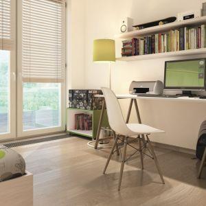 Pokój dla dziecka również utrzymany jest w białym kolorze ocieplonym drewnianym parkietem i obiciem łóżka. Ciekawymi akcentami tego wnętrza są zielona lampa oraz otwarta szafka na kółkach. Fot. Biuro Projektów MTM Styl