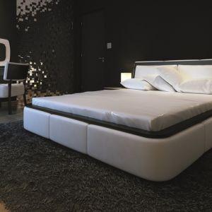 Zupełnie inne wrażenie, niż reszta pomieszczeń, robi czarno-biała sypialnia, w której dominują czarne ściany, ciemny dywan i szafki. To nowoczesne wnętrze rozjaśniają białe obicia łóżka i krzesła. Fot. Biuro Projektów MTM Styl