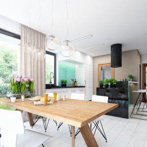 """Centralnym punktem jadalni jest piękny drewniany stół w jesionowym odcieniu. Okalają go nowoczesne, białe krzesła o """"lekkiej"""" konstrukcji. Ważnym elementem dekoracji tej przestrzeni są lampy nad stołem. Fot. Dobre Domy"""