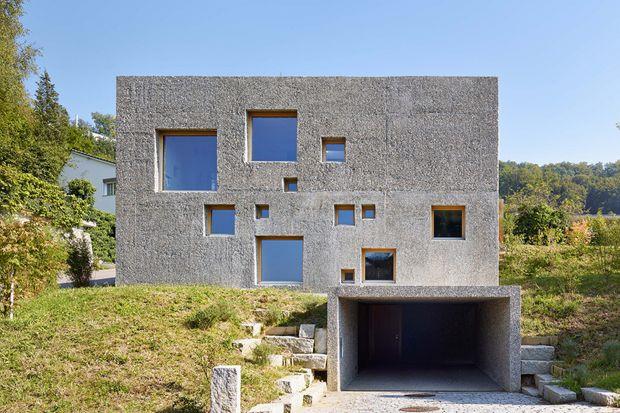 """Ta betonowa 2-piętrowa """"kostka"""" znajduje się w północnej Szwajcarii w dzielnicy Füllinsdorf. Rezydencja z oryginalną, betonową elewacją, wyróżnia się finezyjnie rozmieszczonymi, małymi i dużymi kwadratowymi oknami."""