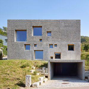 """Ta betonowa 2-piętrowa """"kostka"""" znajduje się w północnej Szwajcarii w dzielnicy Füllinsdorf. Rezydencja z oryginalną, betonową elewacją, wyróżnia się finezyjnie rozmieszczonymi, małymi i dużymi kwadratowymi oknami. Fot. Hannes Henz"""