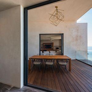 """Elewacja domu została pokryta stiukiem z białego cementu, zmieszanego żywicą pozyskaną z lokalnych drzew """"chukum"""". Dzięki temu fasada domu wyróżnia się oryginalną kolorem i ciekawą strukturą. Fot. Pim Schalkwijk"""