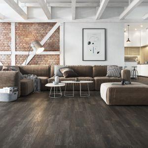 O ile drewniana podłoga w ciemnej tonacji jest dość kłopotliwa z uwagi na konieczność konserwacji, a także uwydatnione wszelkie zarysowania, o tyle z płytkami imitującymi drewno nie mamy żadnego z tych problemów. Fot. Opoczno