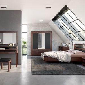 W sypialni Riva wyjątkowy klimat tworzą meble o ciemnej, głębokiej brązowej barwie. Niepowtarzalny dąb burgundzki, który pokrywa drewniane fronty i korpusy w okleinie naturalnej ładnie koresponduje z tkaniną obiciową i ciemnym szkłem Lacobel. Fot. Mebin