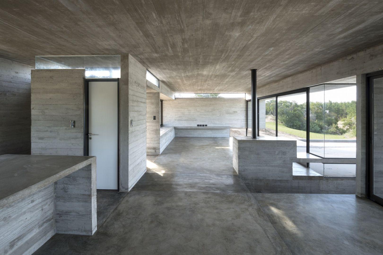 W domu dominuje wypolerowany beton, szykowne szkło oraz aluminiowe ramy. Stoją one w opozycji z surowym betonem imitującym fakturę drewnianej deskęi. Fot. Daniela Mac Adden