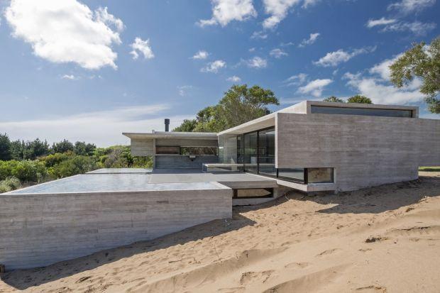 Ten betonowy dom jest położony na opadającej wydmie. Rezydencja jest typowym domem letnim, gdzie rodzina może wspólnie spędzać wakacje. Dlatego najważniejsza w nim jest dobrze przemyślana i zaprojektowana przestrzeń wspólna, gdzie rodzicie wraz