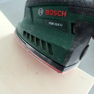 Przy pomocy szlifierki, np. Bosch PSM 10,8 LI, wyszlifuj każdy kawałek sklejki. Pamiętaj o krawędziach, aby nie były nieprzyjemne dla rąk. Potem usuń pył przy pomocy wilgotnej szmatki. Fot. Bosch