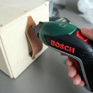 Jednym z wkrętów robimy otwory w skórzanych paskach. Następnie przykręcamy je do skrzynki wkrętarką. Fot. Bosch
