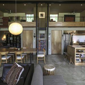 Wnętrze domu zostało zaprojektowane jako jedna wielka otwarta przestrzeń z wydzielonymi strefami. Na dolnym poziomie mieści się otwarta kuchnia połączona z jadalnią i salonem. Fot. Graham Sandelski