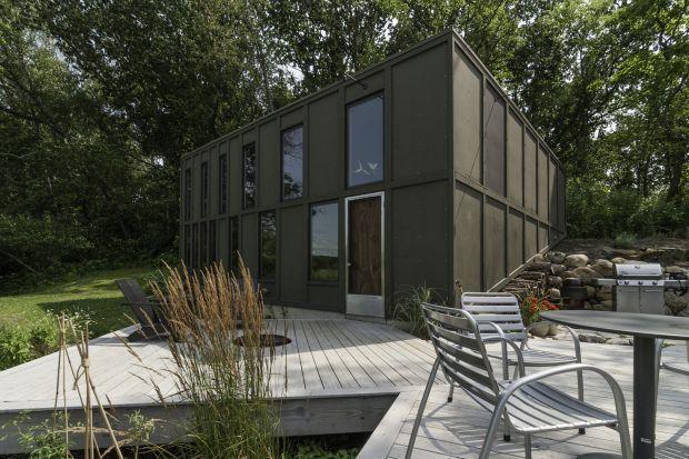 """""""Box"""" jest nietypowym domem, który jest urzeczywistnionym marzeniem właściciela. Pragnął on małego domku z widokiem na rozlewisko, otoczone dziewiczymi terenami podmokłymi. Tak powstała koncepcja domu wzniesionego na wzgórzu z szeregu moduło"""