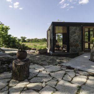 Architekci ze studia Bamesberger Architecture postanowili umieścić dom na zboczu niewielkiego wzgórza. Wiązało się to z wykonaniem wykopu, podczas, którego trzeba było usunąć większe głazy i skały. Obok znajduje się mały magazyn. Fot. Graham Sandelski